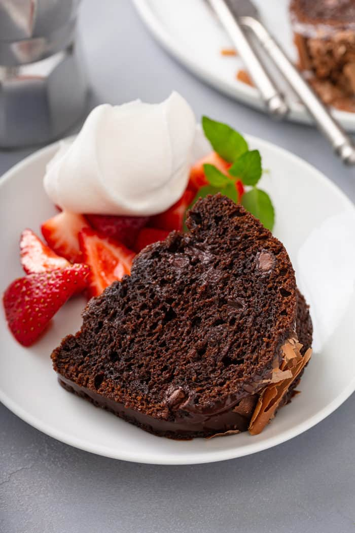 Slice of chocolate bundt cake next to berries and whipped cream on a white plate
