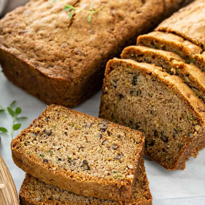 Two loaves of classic zucchini bread on a cutting board, with several slices cut from one of the loaves