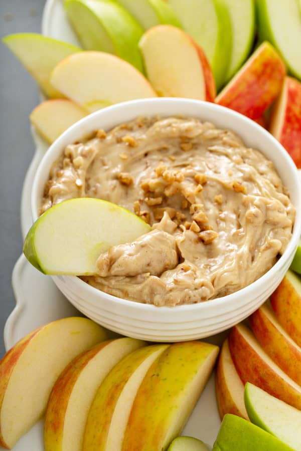 Apple slice dipped into a white bowl of toffee apple dip, surrounded by sliced apples