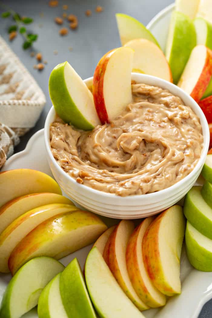 Slices of fresh apples in a bowl of toffee apple dip, surrounded by sliced apples on a platter