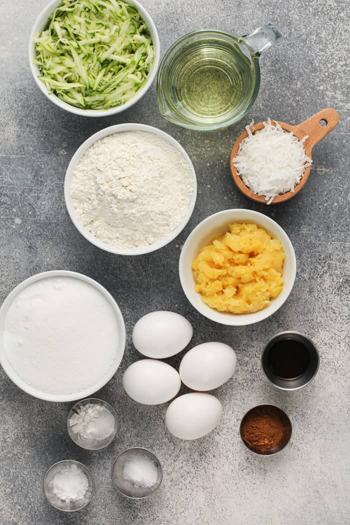 Ingredients for zucchini bundt cake arranged on a gray countertop