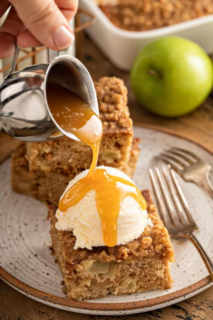 Caramel sauce being poured over a sliced of apple coffee cake topped with ice cream