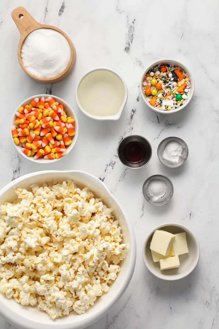 Ingredients for halloween popcorn balls arranged on a marble countertop