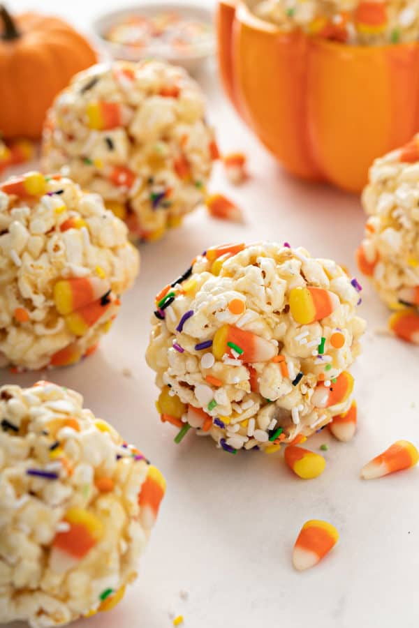 Close up of Halloween popcorn balls scattered on a marble countertop