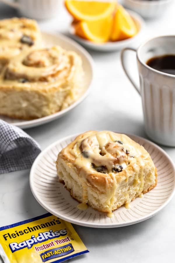 Plated cranberry orange cinnamon roll next to a cup of coffee