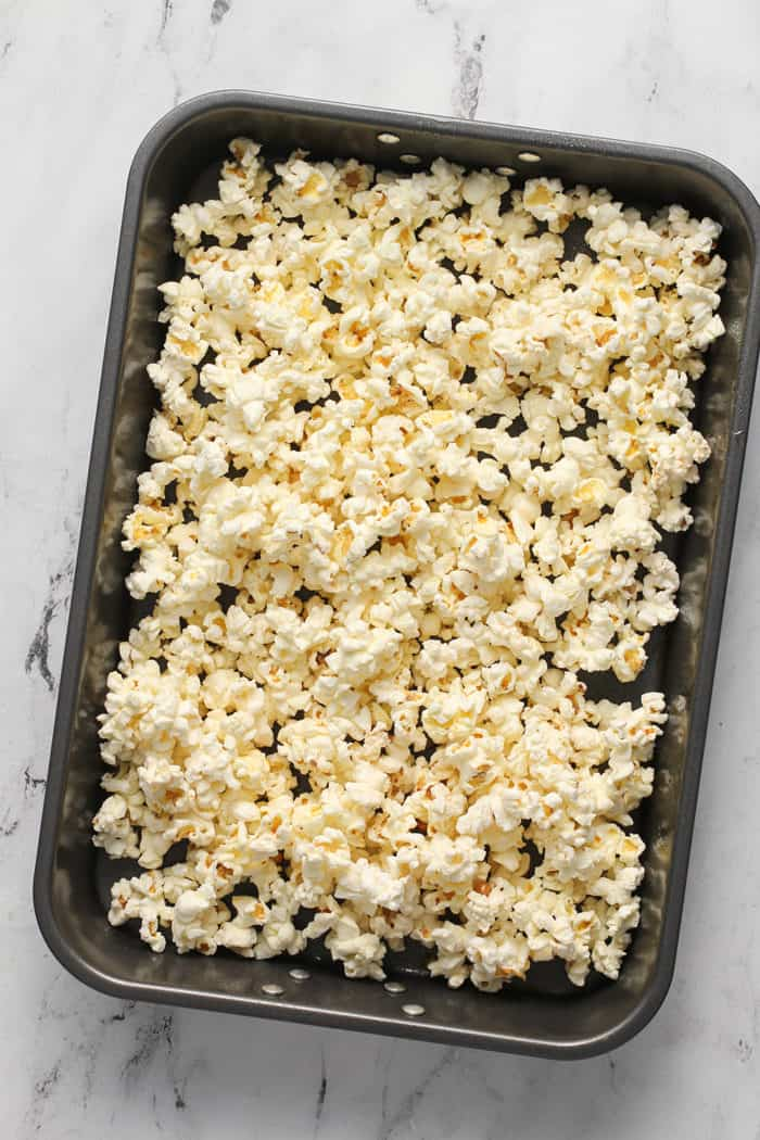 Pan of popped popcorn set on a marble countertop