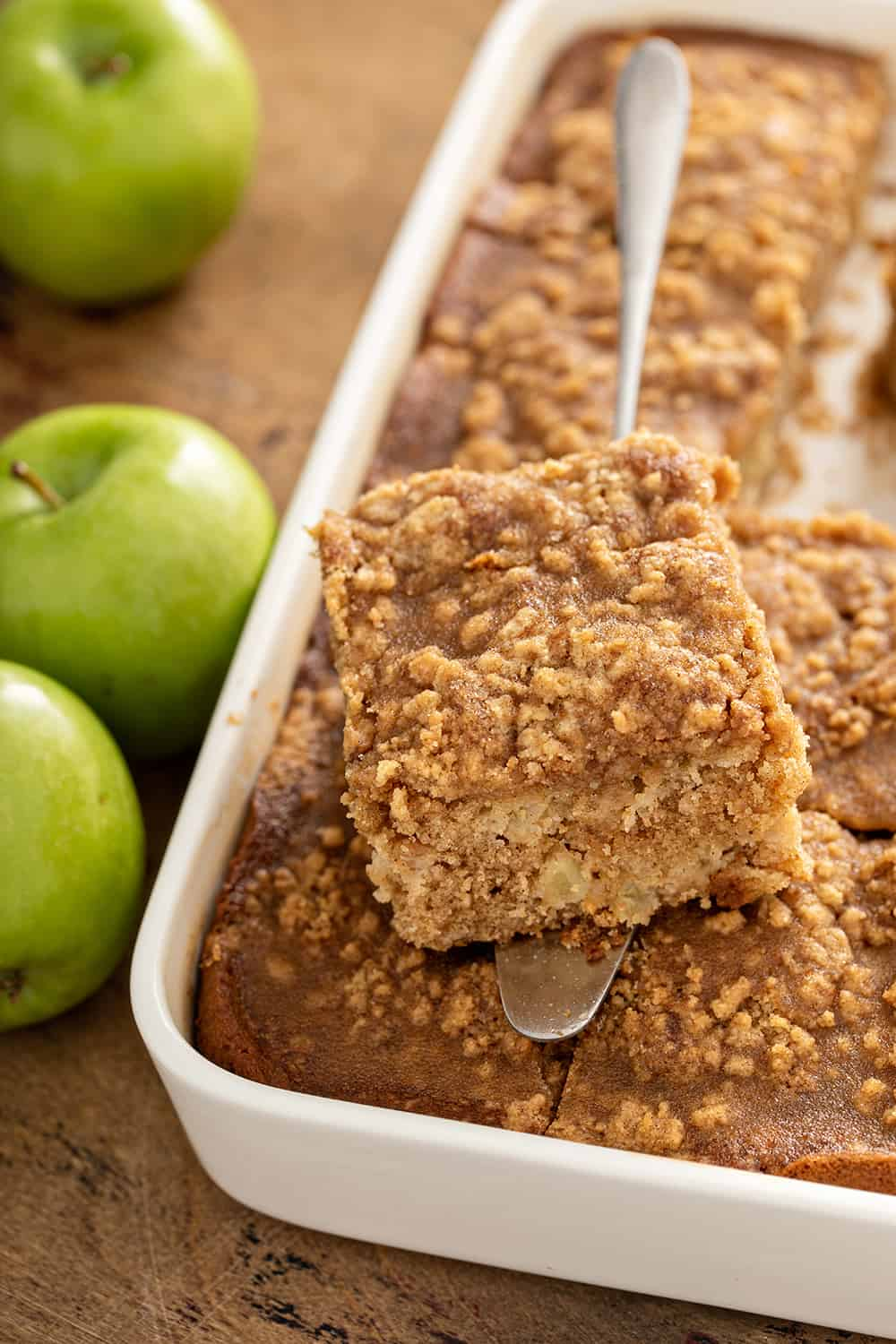 Cake server holding a slice of apple coffee cake over a pan of coffee cake