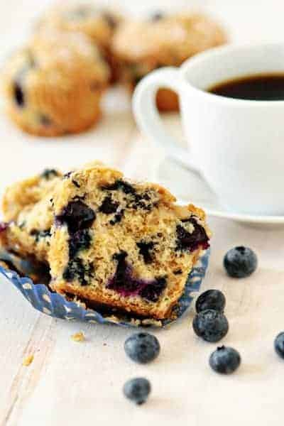 Blueberry lime muffin cut in half on a white surface in front of a cup of coffee and fresh blueberries