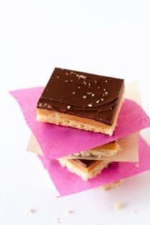 Three pieces of Caramel shortbread stacked with pink and white paper in between