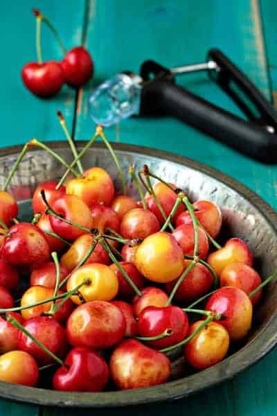 Bowl of fresh cherries in front of a cherry pitter