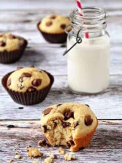Chocolate chip muffin with a bite taken out of it in front of a glass of milk on a wood surface