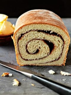 Cut loaf of cinnamon bread on a stone surface with a knife
