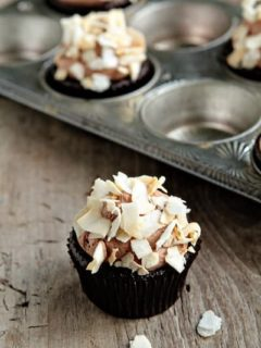 A coconut mocha cupcake in front of a pan of cupcakes on a wood surface
