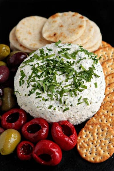 Feta cheese ball next to crackers and olives