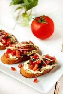 Three pieces of garlic tomato bruschetta on a white plate in front of a tomato