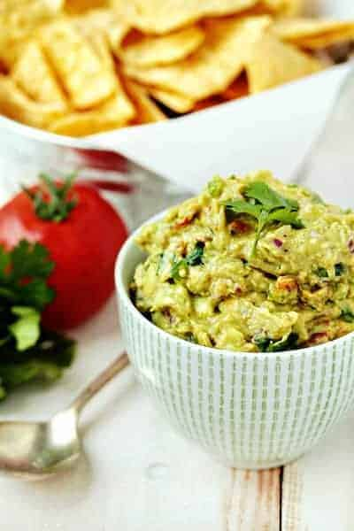 Bowl of spicy guacamole in front of a bowl of chips on a wooden surface