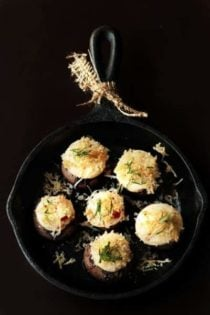 Stuffed mushrooms in a cast iron skillet with a black background