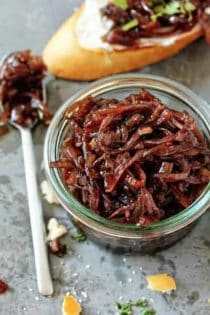 Glass jar full of red onion chutney next to a spoon