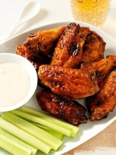 Sweet and spicy baked chicken wings on a plate with celery and a dipping sauce
